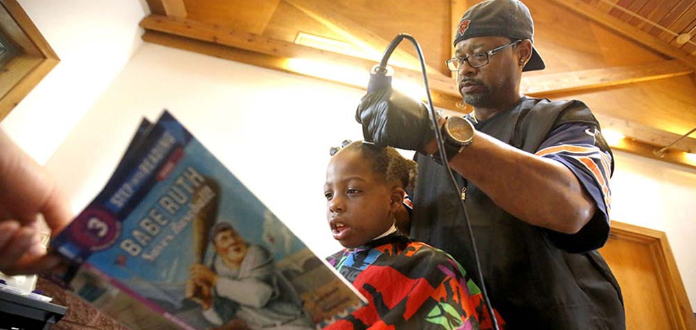 Barbeiro americano corta gratuitamente cabelo de crianças que leem livros para ele