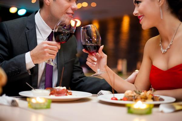 hands of couple toasting their wine glasses over a restaurant ta