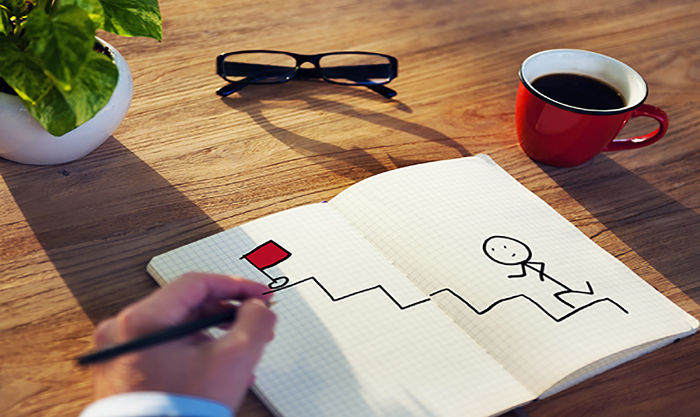 Businessman Drawing Goal Concept on a Note Pad